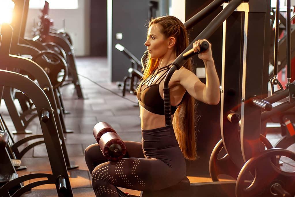 Femme s'entrainant seule sur un plateau musculation
